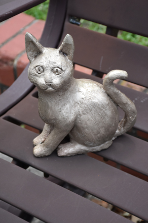 Bronze sculpture of cat on a bench