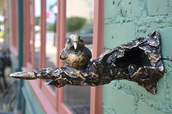 Bronze sculpture of bird on tree limb