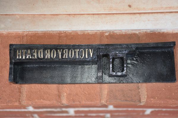 Metallic sign on brick wall